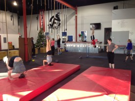 9am CrossFitters working on headstand, forward and backward rolls.