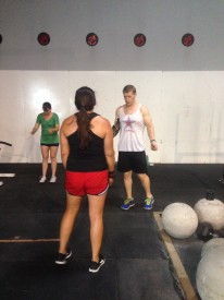 CrossFit Coach, Josh, talks scaling double unders with one member before a workout.